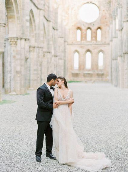 Bride in a Rara Avis Wedding Dress and Groom in Black Tie Suit Kissing in an Open Air Church Wedding Venue