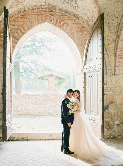 Bride in a Rara Avis Wedding Dress and Groom in Black Tie Suit Embracing