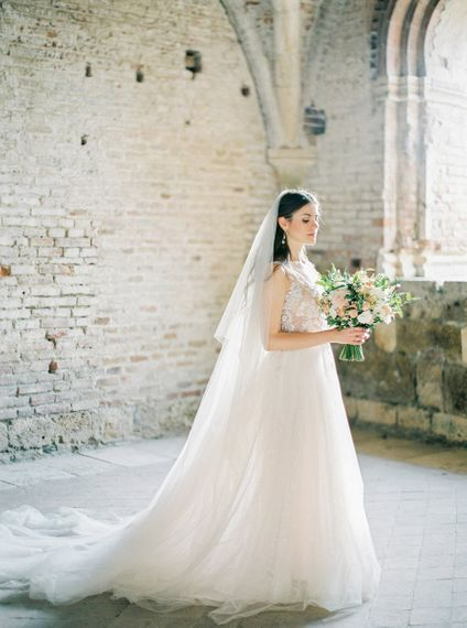 Bride in a Rara Avis Wedding Dress with Peach and White Wedding Bouquet