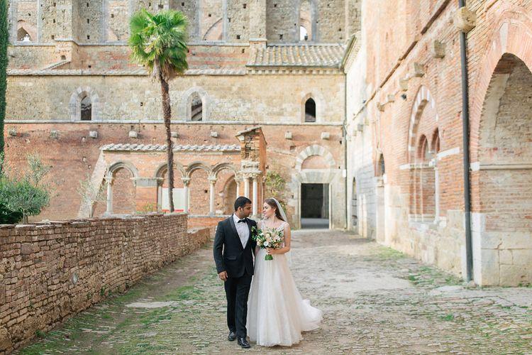 Bride in a Rara Avis Wedding Dress and Groom in Black Tuxedo Walking Through Their Historic Wedding Venue