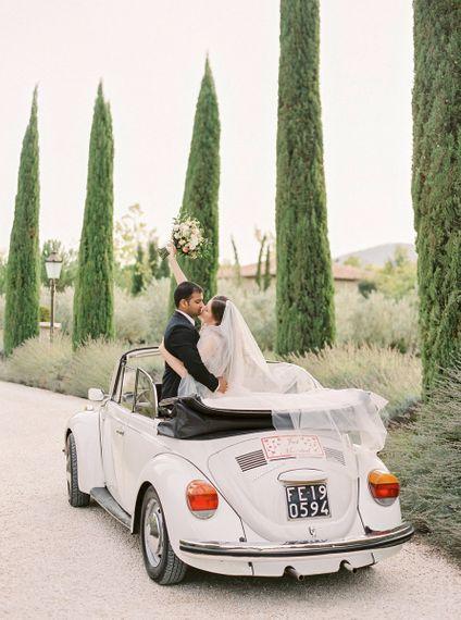 Bride in a Rara Avis Wedding Dress and Groom in Black Tuxedo in Their Convertible Beetle Wedding Car