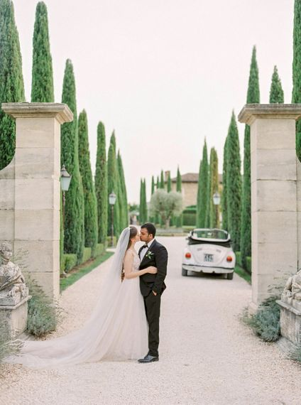 Bride in a Rara Avis Wedding Dress and Groom in Black Tuxedo Kissing with the Tuscan Countryside as their Backdrop