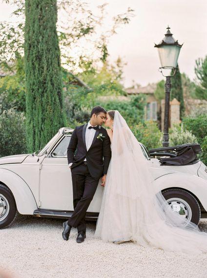 Bride in a Rara Avis Wedding Dress and Groom in Black Tuxedo next to their Convertible Beetle Wedding Car