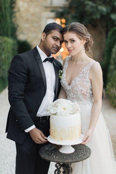 Bride and Groom with Their Elegant Wedding Cake