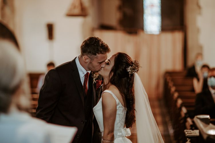 Bride and groom kissing at socially distanced church wedding ceremony