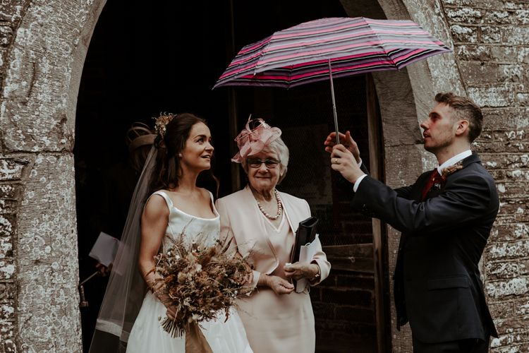 Groom sheltering his bride with an umbrella