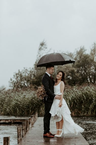 Bride and groom standing under an umbrella at September 2020 Wedding