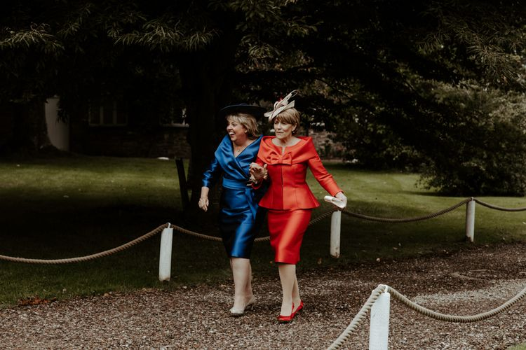 Mother of the bride and groom in red and blue dresses