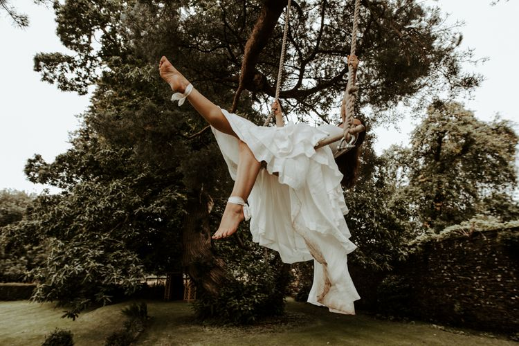 Bride swinging on a trapeze in layered skirt wedding dress