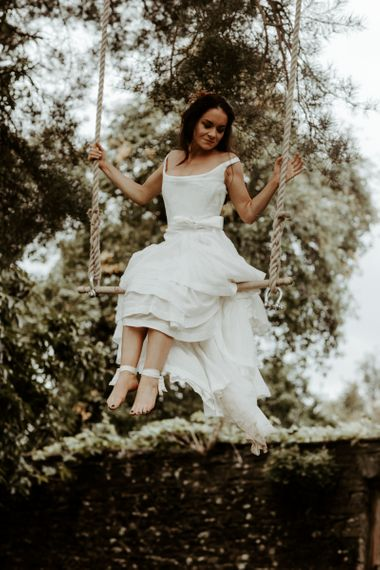 Bride swinging on a trapeze in high low wedding dress