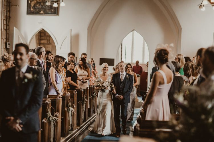 Bride walks down the aisle at church ceremony
