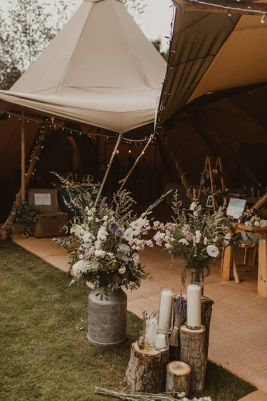 Teepee for wedding reception entrance with flowers in milk churns