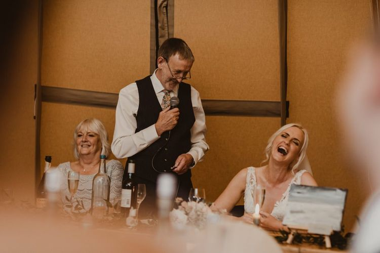 Bride laughs at wedding speeches