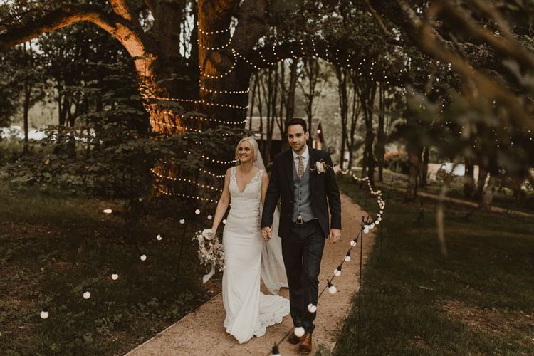 Bride and groom walk down pathway lit by fairy lights