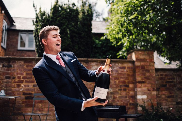 Groomsman in Navy Three Piece Suit Popping a Magnum of Champagne