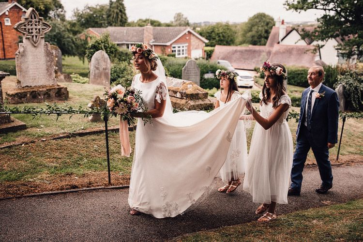 Bride in Walking Through the Church Courtyard with her Flower Girls in Noble and Wright Separates
