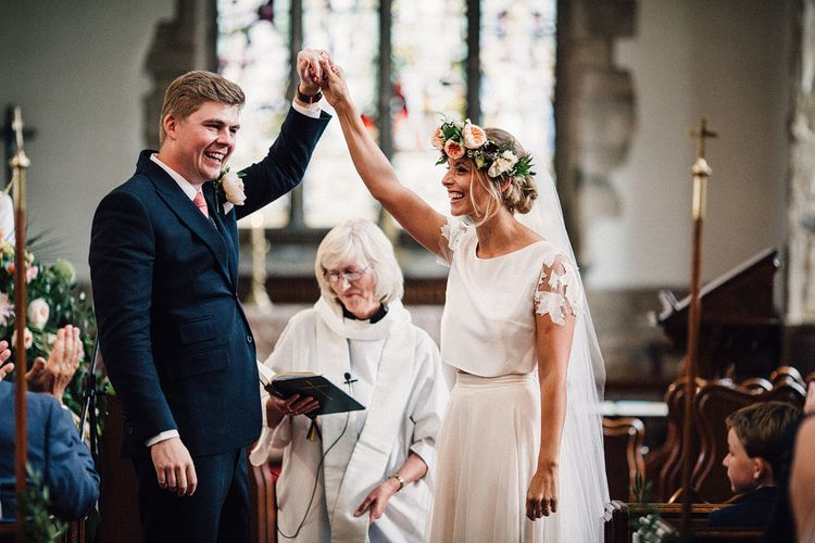 Bride in Noble and Wight Bridal Separates and Flower Crown  Holding Her Grooms Hand at the Altar