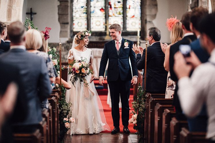 Bride in Noble and Wight Separates and Groom in Three Piece  Navy Suit Walking Up the Aisle