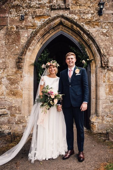 Bride in Noble and Wight Separates and Groom in Three Piece  Navy Suit Outside the Church