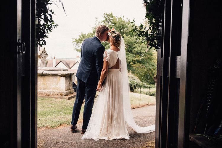 Bride in Noble and Wight Separates and Groom in Three Piece  Navy Suit Kissing Outside the Church