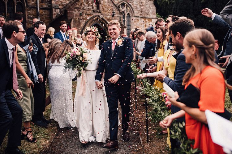 Bride in Noble and Wight Separates and Groom in Three Piece  Navy Suit Confetti Moment Outside the Church
