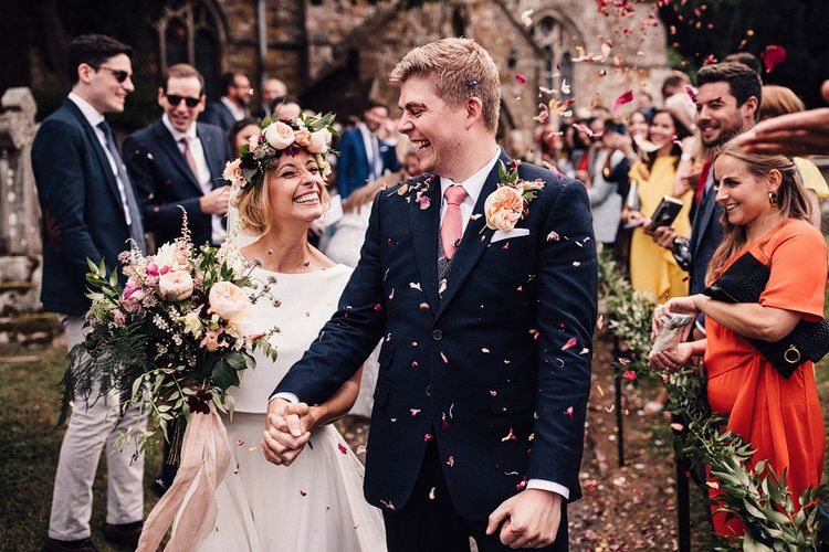 Laughing Bride in Noble and Wight Separates and Groom in Three Piece  Navy Suit Confetti Moment Outside the Church