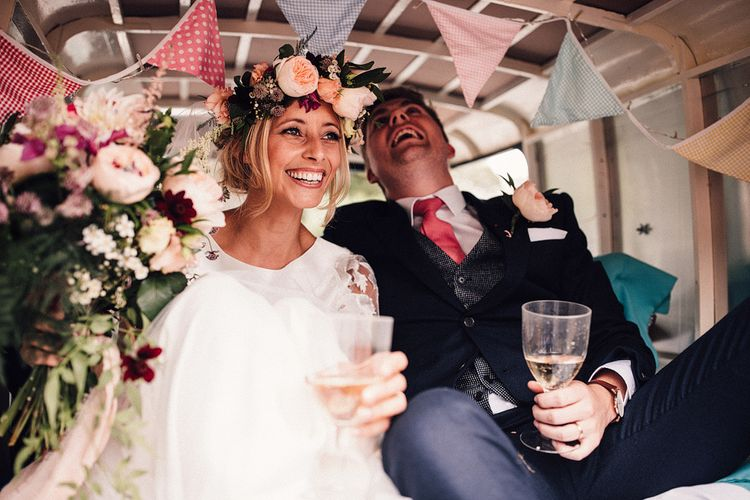 Laughing Bride in Noble and Wight Separates and Groom in Three Piece  Navy Suit Inside Their Wedding Car