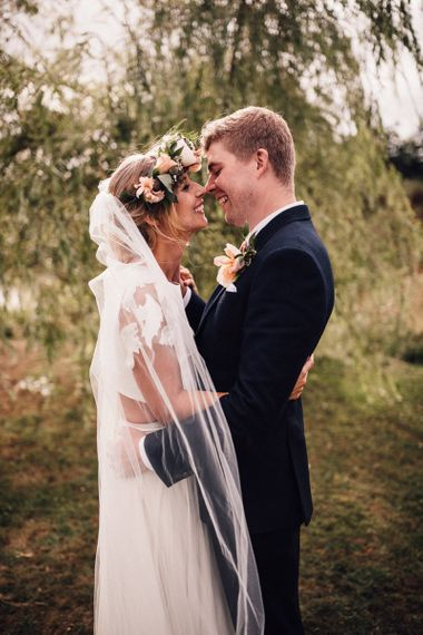 Bride in Noble and Wight Separates and Groom in Three Piece Navy Suit Embracing