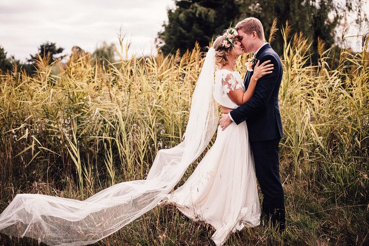 Bride in Noble and Wight Separates and Groom in Three Piece Navy Suit Kissing in a Field