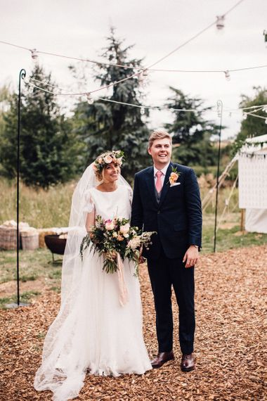 Bride in Noble and Wight Separates with Flower Crown and  Bouquet Standing Next to her Groom in a  Three Piece Navy Suit