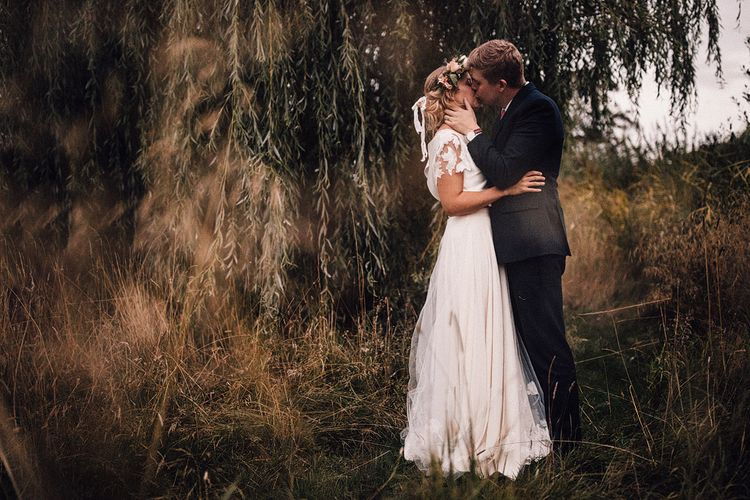 Bride in Noble and Wight Separates with Flower Crown Kissing her Groom in a  Three Piece Navy Suit