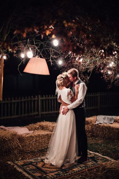 Bride in Noble and Wight Separates with Open Back Top and Groom Kissing under Festoon Lights