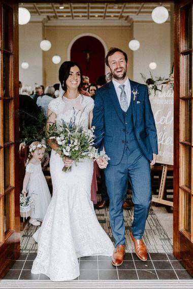 Bride in Jesus Peiro wedding dress with cap sleeves and wild flower bouquet