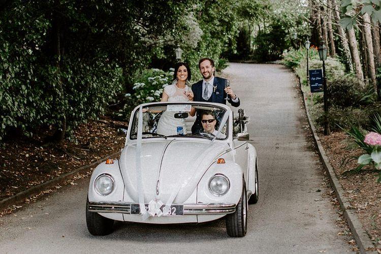 Vintage wedding car with bride and groom