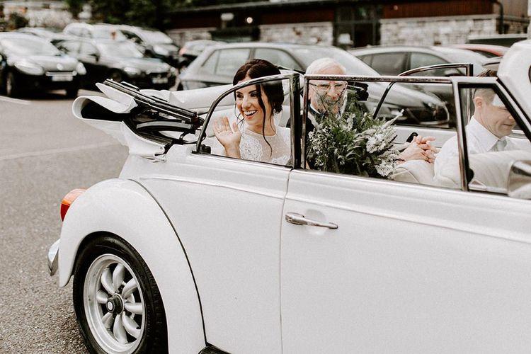 Bride arrives to wedding ceremony in Jesus Peiro wedding dress and white vintage wedding car