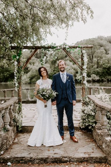 Bride in Jesus Peiro wedding dress with groom under wooden arch decorated in flowers