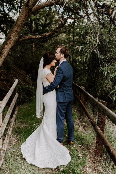 Bridal updo with mid-length veil and Jesus Peiro wedding dress