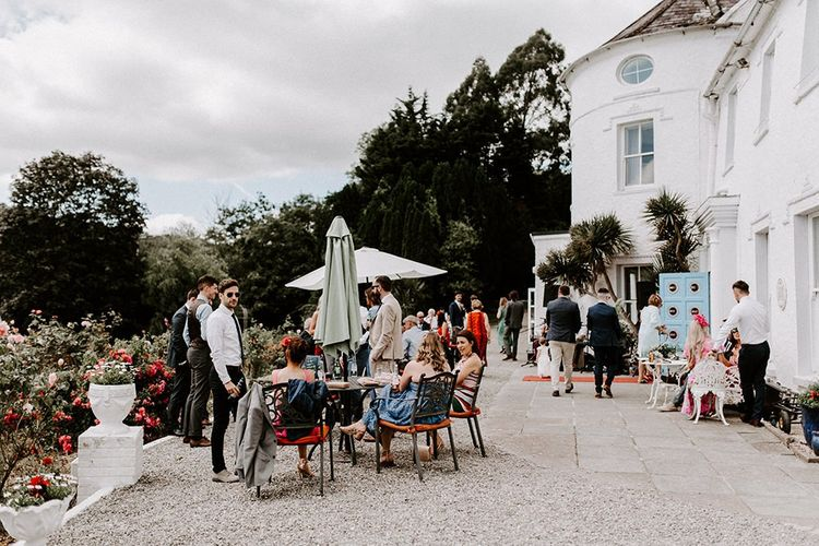 Guests enjoy drinks outside Innishannon House wedding venue
