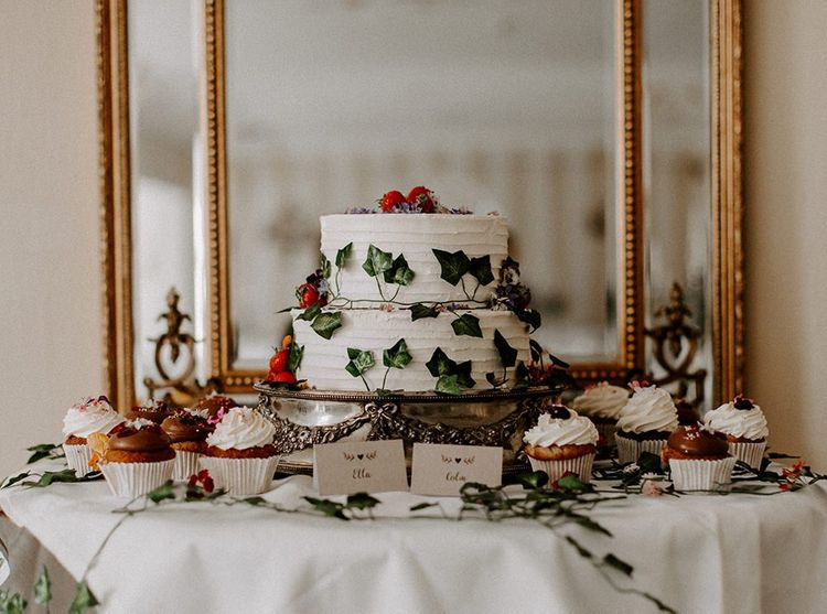 White wedding cake with foliage decor with cupcakes surrounding