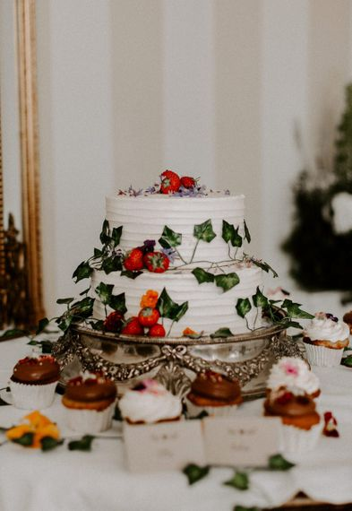 White wedding cake with foliage and berries