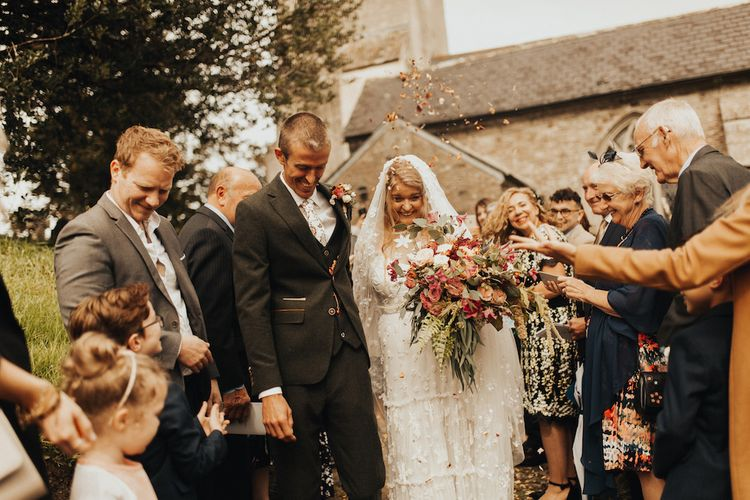 Confetti exit for groom and bride in Eliza Jane Howell wedding dress