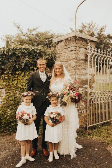 Bride in Eliza Jane Howell wedding dress with groom and flower girl daughters