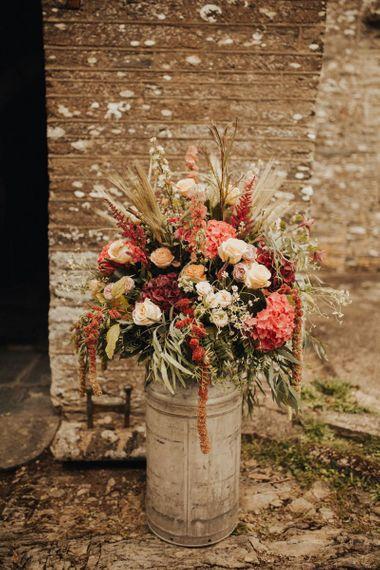 Rustic wedding flowers in milk churn