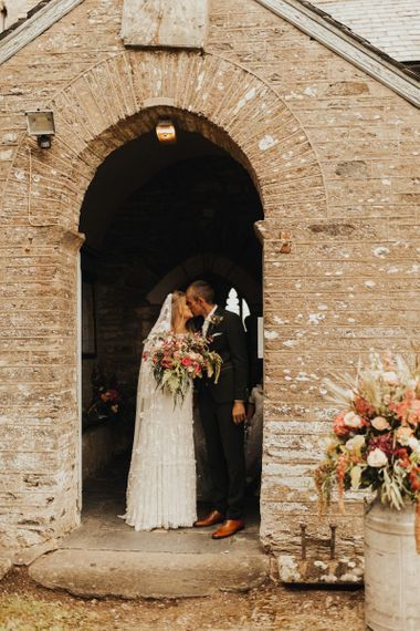 Bride in Eliza Jane Howell wedding dress kisses groom outside church