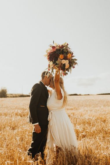 Bride changes from Eliza Jane Howell dress to Ghost wedding dress clutching rustic bouquet