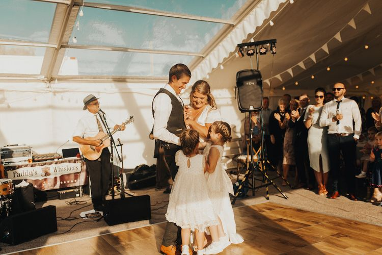 Bride in Eliza Jane Howell wedding dress and groom with their daughters dancing