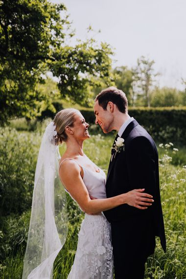 Bride and Groom Embrace with Homemade Veil and Bridal Two Piece