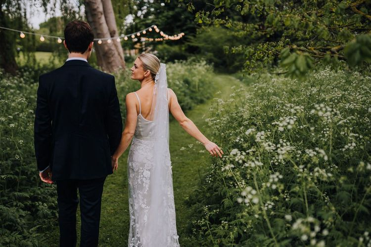 Bride and Groom Walking Through Orchard Filled with Cow Parsley and Bridal Two Piece