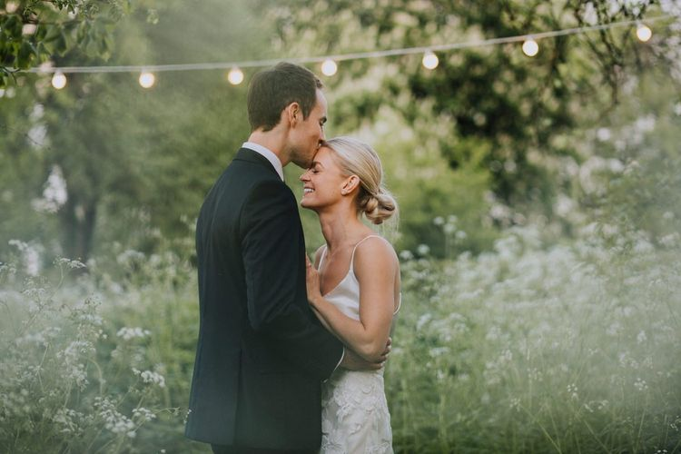 Bride and Groom Embrace with Fairy Lights