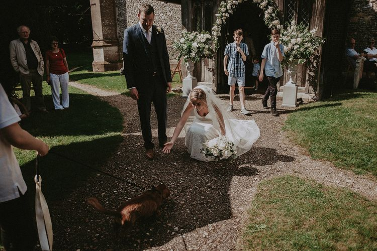 Bride and Groom Greeting Their Pet Dog in The Church Courtyard After The Wedding Ceremony